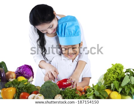 Asian mother is teaching her son to cut vegetable at home - stock photo