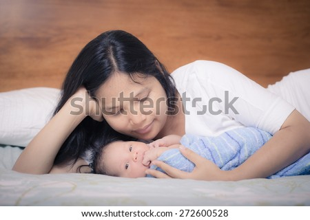 Asian mother lays on her bed in her bedroom with her freshly bathed mixed race 10 day old newborn baby boy wrapped in a clean blue towel - stock photo
