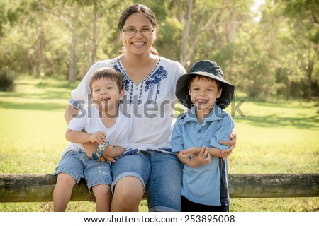 Asian mother outdoors with her 2 mixed race Asian Caucasian sons on the older brother's first day of school - stock photo