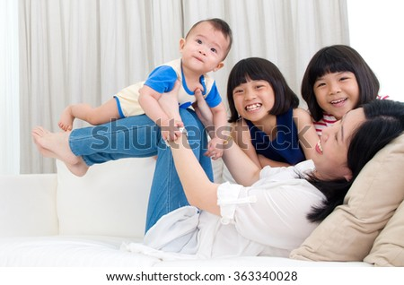 Asian mother playing with her children  - stock photo