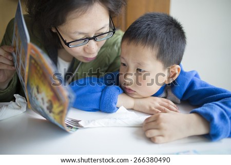 Asian mother reading book for son