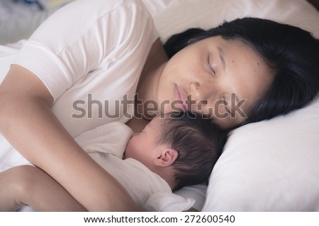 Asian mother sleeps peacefully on her bed with her mixed race 10 day old newborn baby boy in her bedroom - stock photo