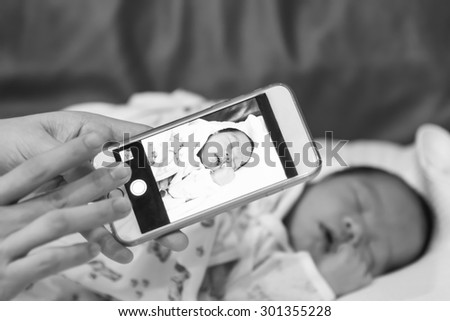 Asian mother take a photo of her baby female son with smart phone focused on the device black and white - stock photo