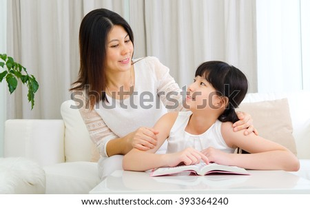 Asian mother talking to her daughter - stock photo