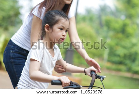 Asian Mother teaching daughter cycling at the park in the evening - stock photo