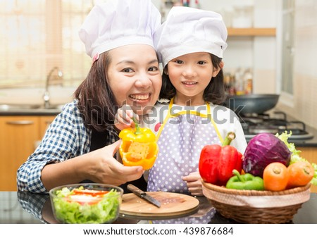 Asian mother teaching daughter making salad in kitchen,Cooking  concept of happy asian little girl and mother making salad for dinner and chopping paprika on cutting board with knife in kitchen