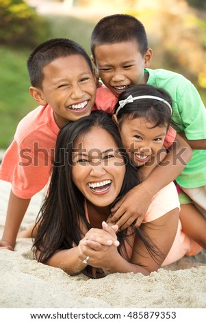 Asian mother with her children at the beach.