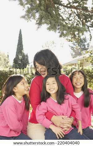 Asian mother with three young daughters laughing outdoors - stock photo