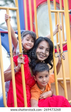 Asian mother with two young children in the playground - stock photo