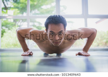 Asian muscular guy doing push-ups exercise on the floor