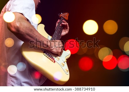 asian musician playing electric guitar with colourful bokeh light on stage for music background - stock photo