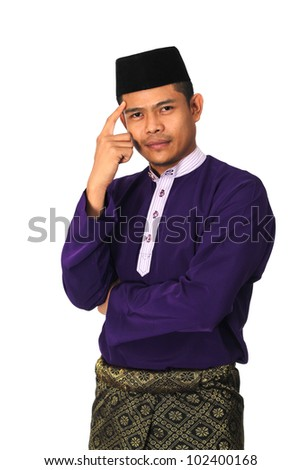 Asian muslim male with traditional Malay costume in thinking action, Baju Melayu - stock photo
