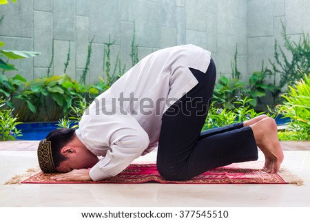 Asian Muslim man praying on carpet with beads chain wearing traditional dress - stock photo