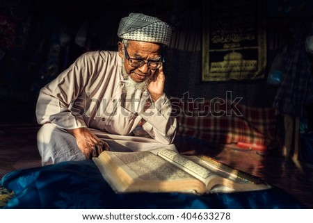 Asian Muslim man reading Koran or Quran