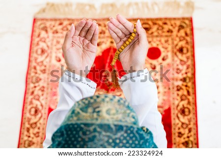 Asian Muslim woman praying on carpet with beads chain wearing traditional dress - stock photo