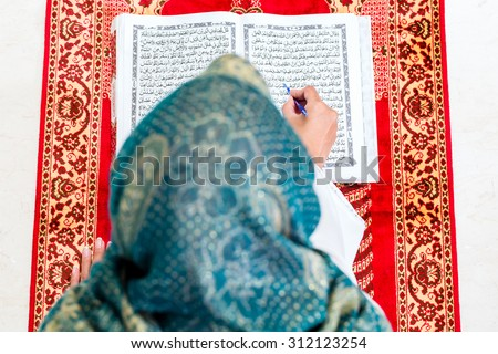 Asian Muslim woman reading Koran or Quran on praying carpet wearing traditional dress - stock photo