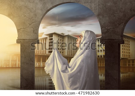 Asian muslim woman wearing veil on mosque and pray to god.