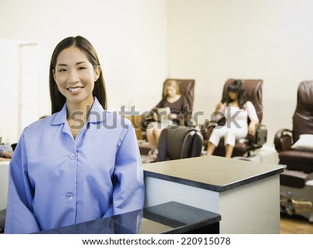 Asian nail technician at counter - stock photo