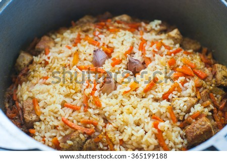 Asian national rice food called pilaf cooked with fried meat, closeup