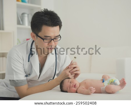 asian newborn at hospital with doctor - stock photo