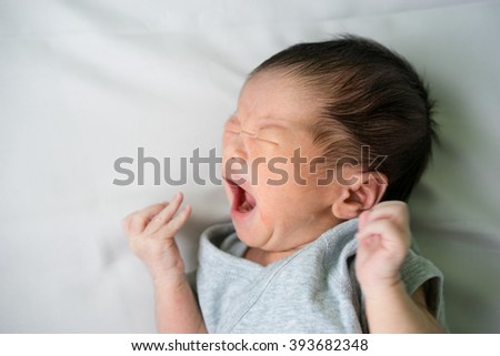 Asian newborn baby lying and crying in his bed - stock photo