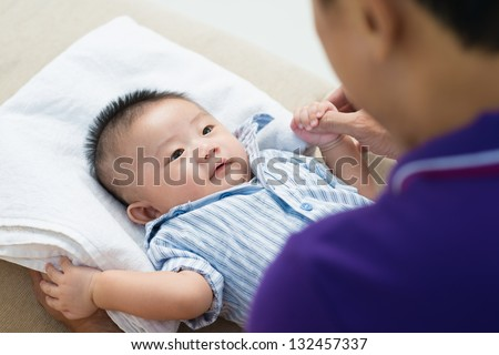 Asian newborn looking at his father