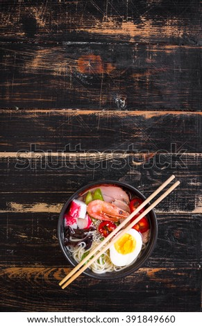 Asian noodle soup in a black bowl with chopsticks on a dark textured wooden background. With meat, boiled egg, shrimp, tofu, mushroom, chili, green onions, sesame seeds. Space for text. Overhead - stock photo
