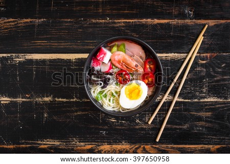 Asian noodle soup in a black bowl with chopsticks on a dark textured wooden background. With meat, boiled egg, shrimp, tofu, mushroom, chili, sesame seeds. Top view - stock photo