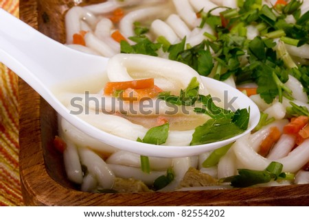 Asian noodle soup in a wooden bowl and a white spoon. - stock photo