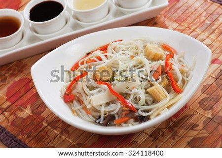 Asian noodle soup with vegetables served in bowl with various sauces - stock photo