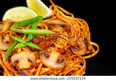Asian noodle with roast mushroom, lime and green onion isolated on black background - stock photo