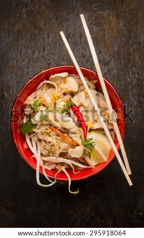 Asian noodles with chopstick, chicken and sprouts on dark wooden background, top view - stock photo