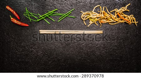 Asian noodles with chopstick, red chili ,chopped chives on black slate background, top view, banner for website - stock photo