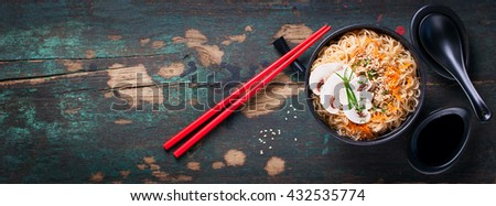 Asian noodles with vegetables and mushrooms, soy sauce, sticks on a dark background, top view with copy space - stock photo