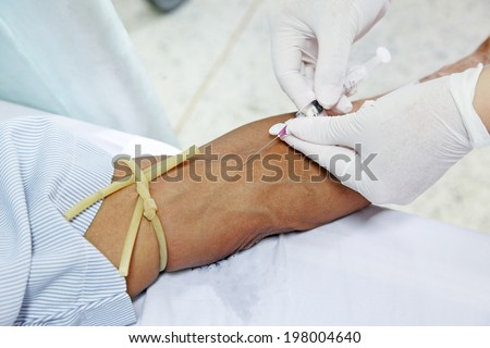asian nurse inject at patient's arm for intravenous fluid  - stock photo