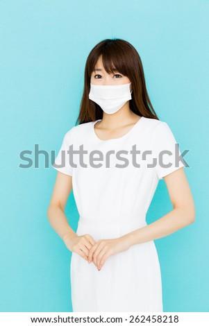 asian nurse wearing doctor mask on blue background - stock photo