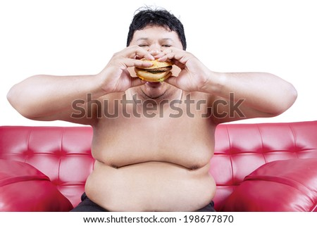 Asian obese person eating hamburger isolated over white - stock photo