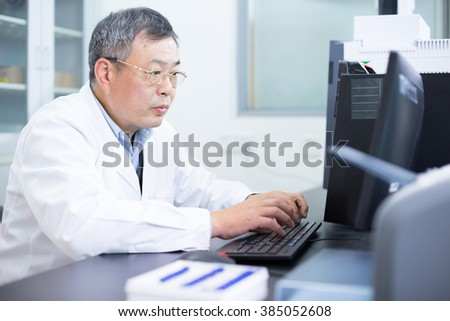 Asian old man analysis chemical experimental data in computer in lab - stock photo