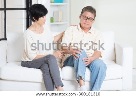 Asian old man knee pain, sitting on sofa with wife at home. Chinese family, senior retiree indoors living lifestyle. - stock photo