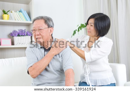 Asian old man shoulder pain, sitting on sofa , daughter massaging father shoulder. Chinese family, senior retiree indoors living lifestyle at home. - stock photo