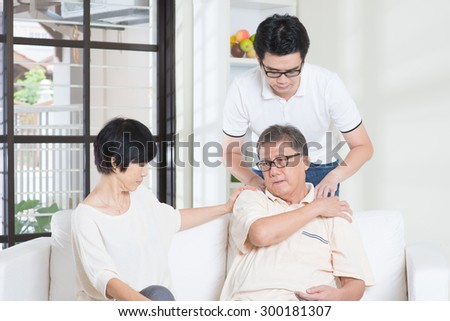 Asian old man shoulder pain, sitting on sofa with wife, son massaging father shoulder. Chinese family, senior retiree indoors living lifestyle at home.