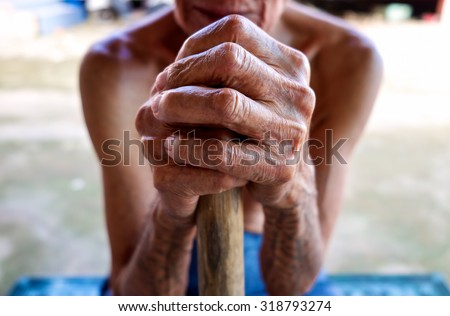 Asian old man skinny sitting with his hands on a walking stick. - stock photo