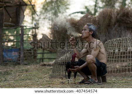 Asian old man smoking with Thai gamecock Countryside Lifestyle concept