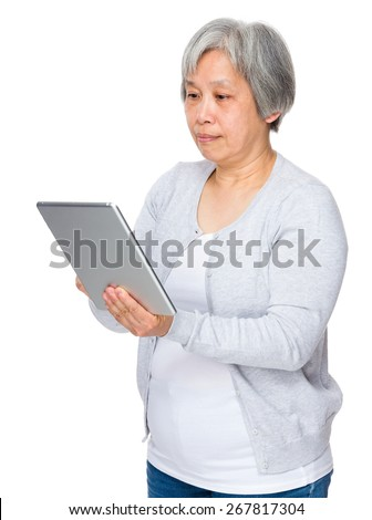 Asian old woman use of tablet - stock photo