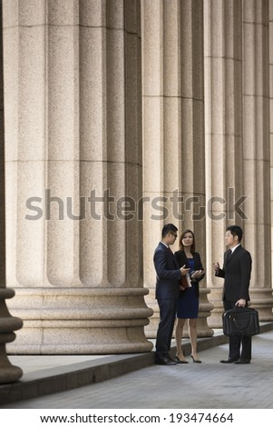 Asian or Chinese business colleagues. Professional Lawyer or business team outside a Colonial building.  - stock photo