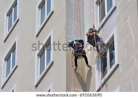 Asian painter hanging to paint with high building