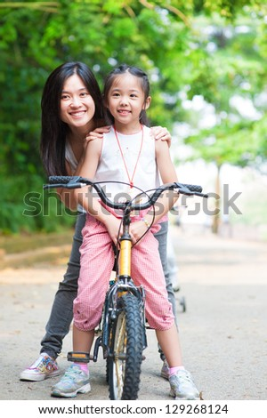 Asian parent and child riding a bike - stock photo