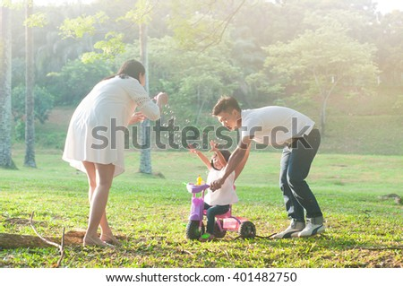 Asian parent and daughter blowing bubbles in the park - stock photo