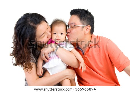 asian parent kissing their baby girl - stock photo