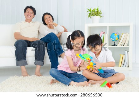 Asian parent looking at their children playing building blocks - stock photo